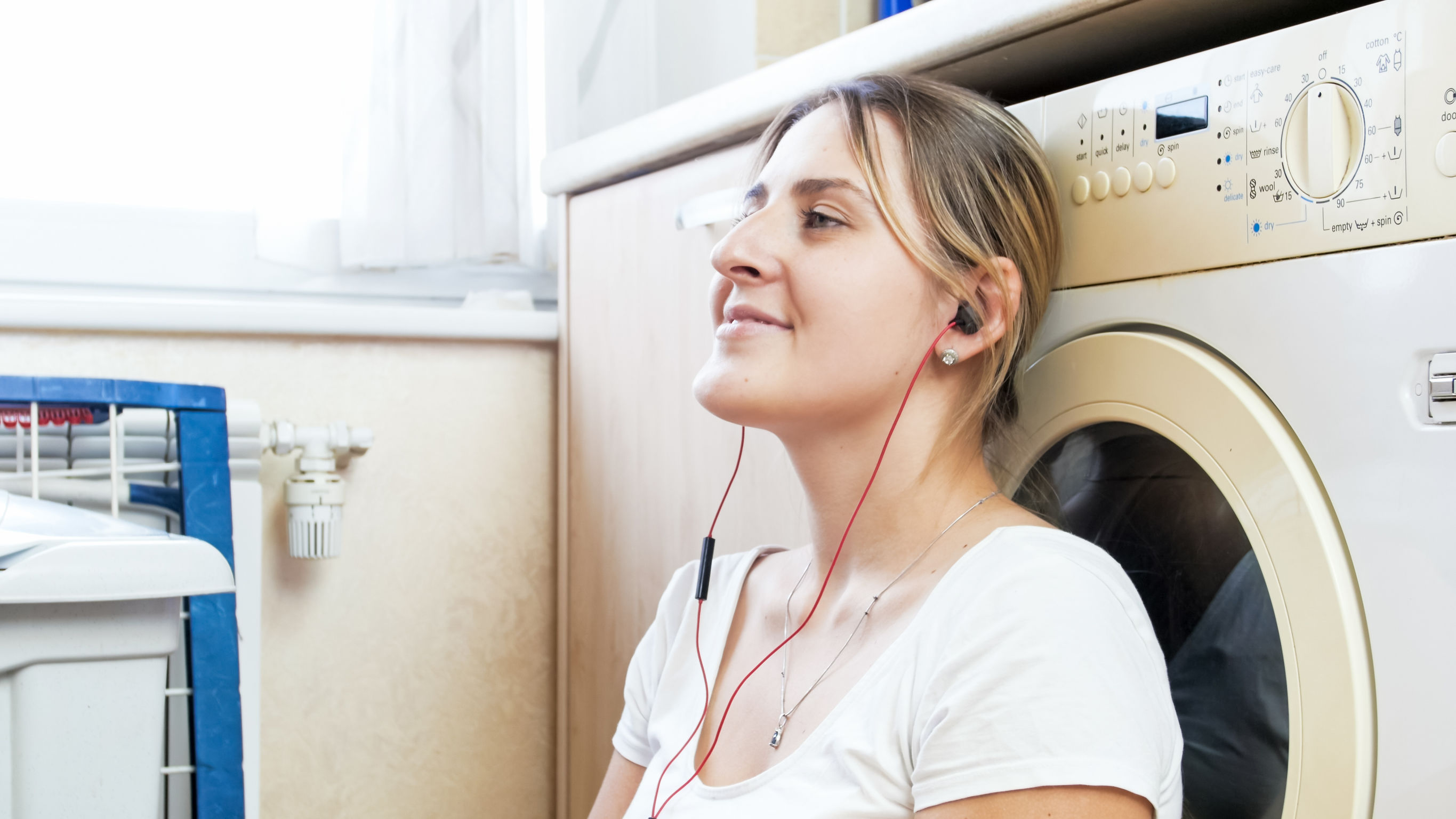 Portrait of beautiful housewife with earphones leaning on washing machine at laundry