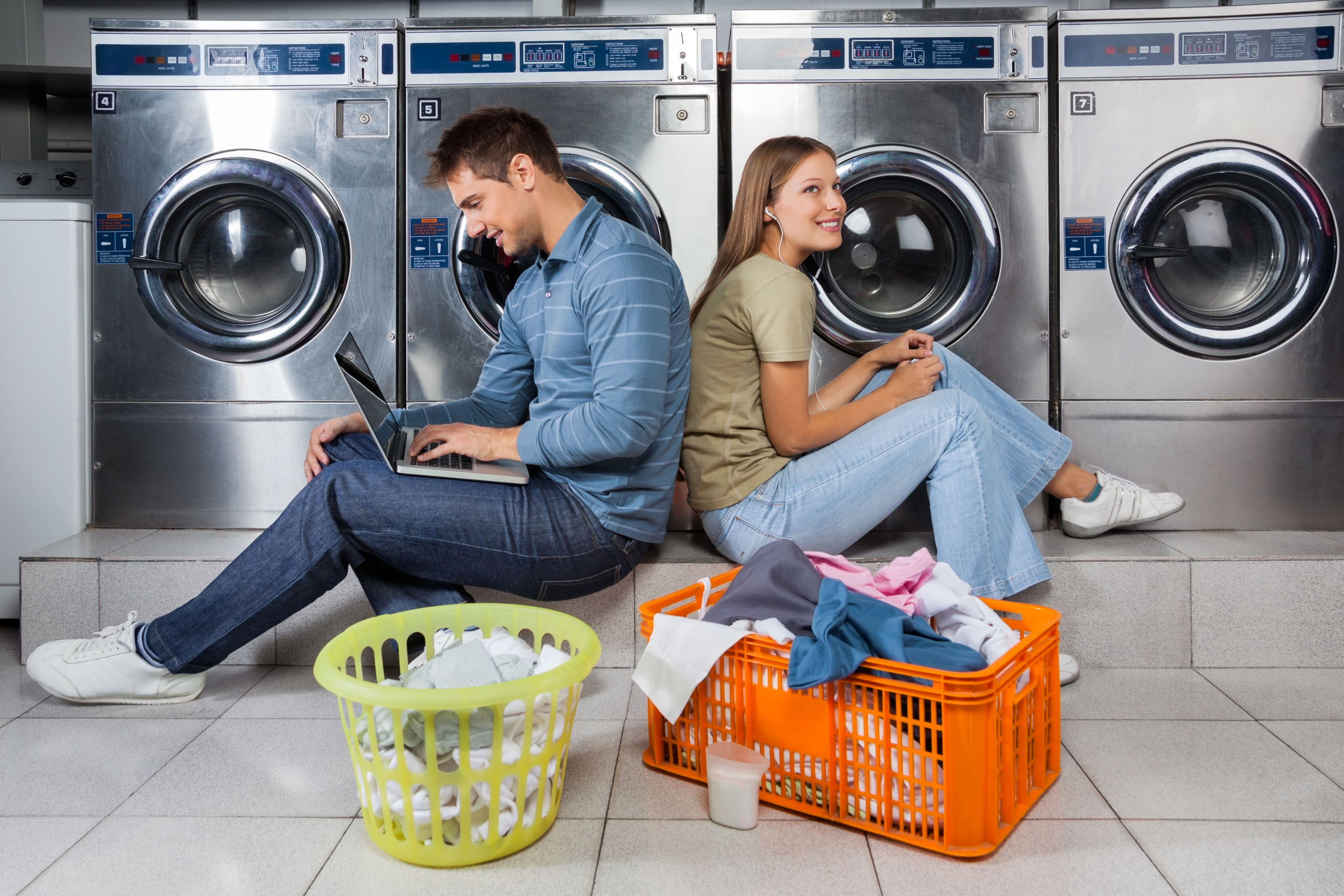 Man using laptop and woman listening to music while sitting back to back at laundry